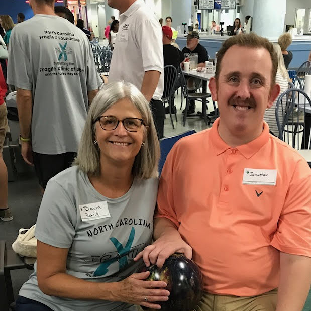 Dawn Rohlik holding a bowling ball with a gentleman at the NC Fragile X Bowl-A-Thon.